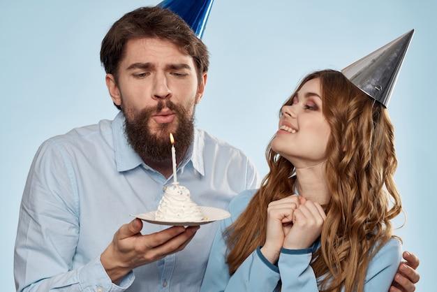 誕生日にカップケーキとお祝いの帽子のキャンドルで男女が楽しんで、休日を一緒に祝う
