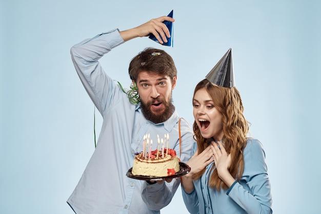 カップケーキとお祝いキャップのキャンドルで誕生日に男女が楽しんで、一緒に休日を祝う