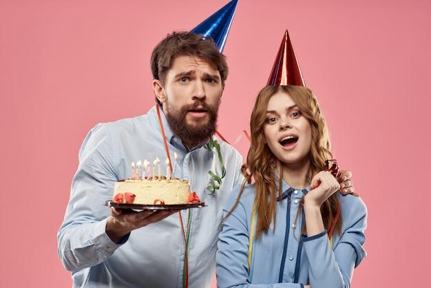 Мужчина и женщина на день рождения с кексиком и свечкой в праздничной шапочке веселятся и отмечают праздник вместе