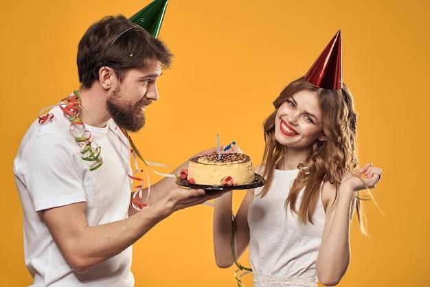Мужчина и женщина в день рождения с кексом и свечой в праздничной шапочке веселятся