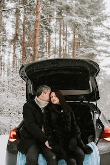 車のトランクの降雪で雪に覆われた森の背景に男と女