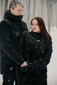 降雪の中の雪に覆われた森を背景に男と女