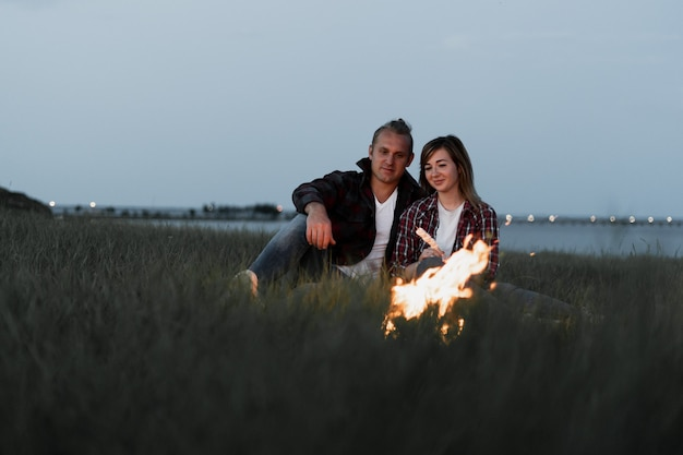 Мужчина и женщина сидят вечером у костра
