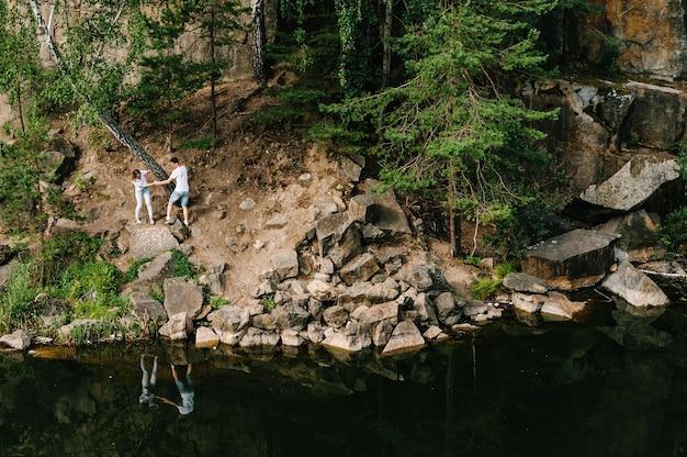男と女が岩に沿って歩き、森と湖の近くの木の下を這う
