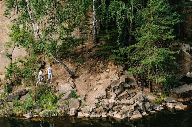 男と女が森と湖の近くの岩に沿って歩く