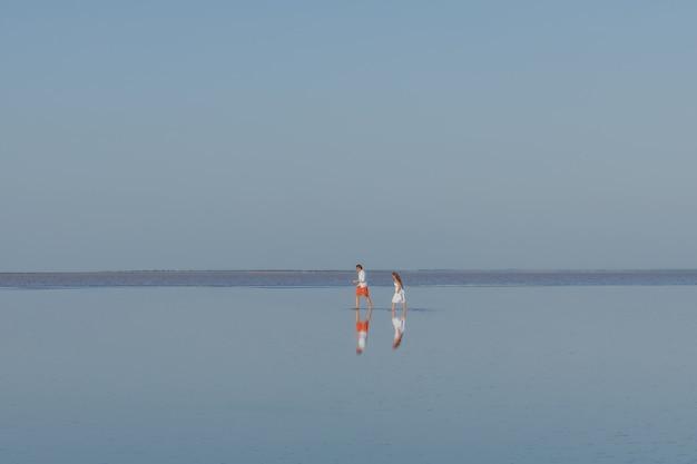 男と女が湖のなめらかな水の上を歩く