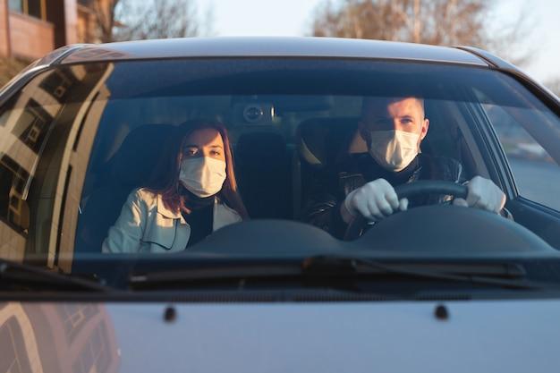 車の運転中にバクテリアやウイルスから身を守るために医療用マスクとゴム手袋を着用している男女。車の中で覆面をした男性。コロナウイルス、covid-19