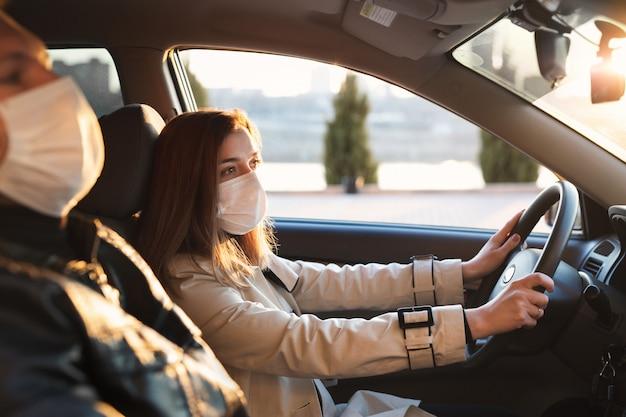 車の運転中にバクテリアやウイルスから身を守るために医療用マスクとゴム手袋を着用している男女。ホイールの後ろの女性。コロナウイルス、コビッド-19