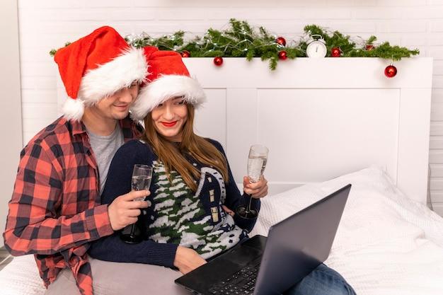 샴페인을 든 남자와 여자는 랩톱에서 온라인으로 의사 소통합니다. 산타 모자에 샴페인을 마시는 커플