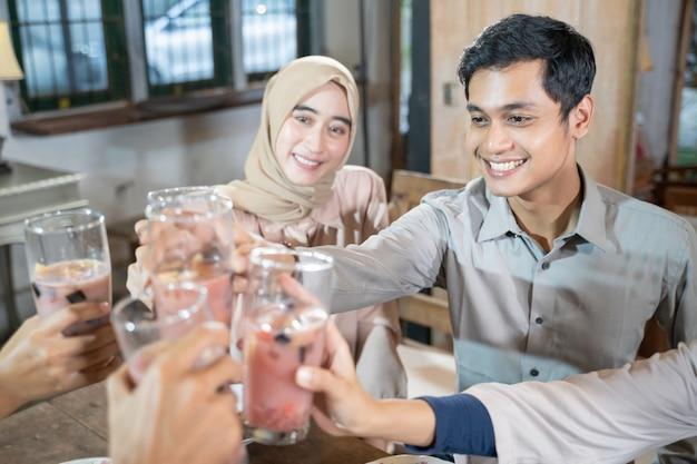 男と女が一緒に断食をしながら乾杯のためにフルーツアイスのグラスを祝って育てます