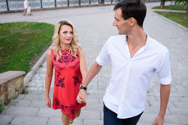 Влюбленные мужчина и женщина гуляют по парку и обнимаются.