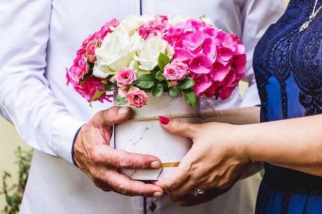男性と女性がたくさんの花を手に持ち、ごちそうの際に挨拶をします_