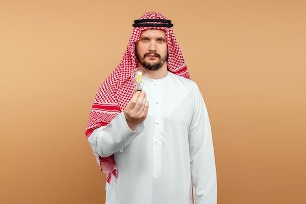 Араб мужчина держит в руке лампочку в национальном костюме. идея концепции, мысль.