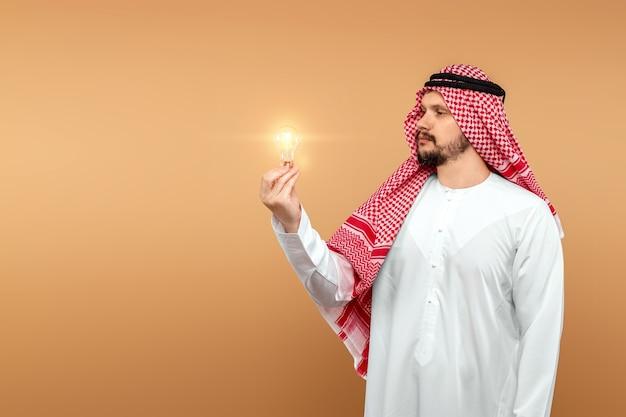 남자 아랍은 그의 손에 전구를 들고 민족 의상을 보유하고 있습니다. 개념 아이디어, 생각.