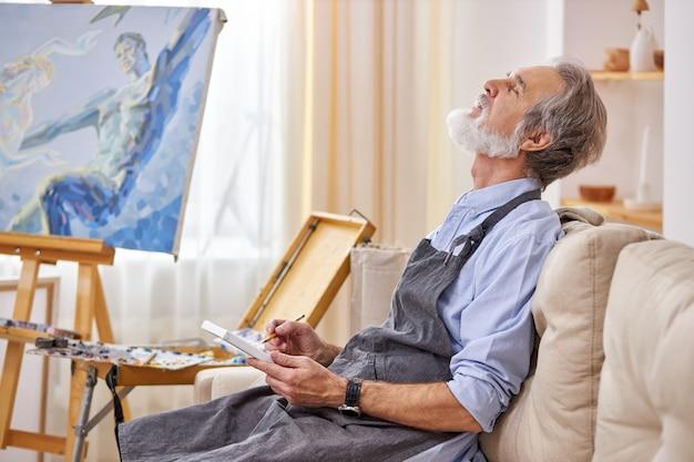 한 남자 예술가가 뮤즈가 걸작을 만들기를 기다리고 있으며, 생각에 빠져 예술 스튜디오에서 소파에 앉아 생각하고 있습니다.