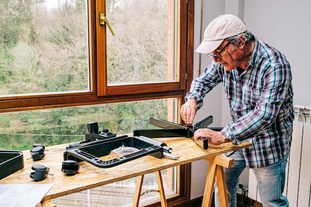 在宅勤務用のオフィスチェアキットを組み立てる男性。