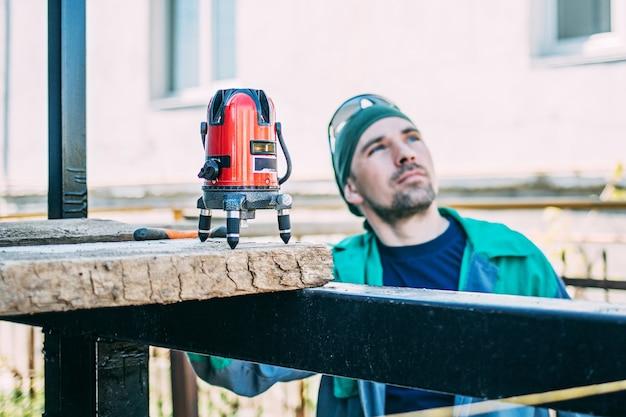 Мужчина на стройке проверяет работу лазерным уровнем