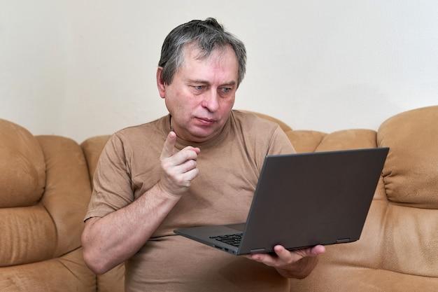 Мужчина в возрасте сидения на девани просматривает новости на ноутбуке.