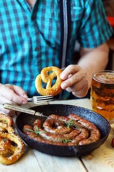 ビール1杯、プレッツェル、ソーセージ付きのフライパンを持つテーブルの男。オクトーバーフェストのお祝い。