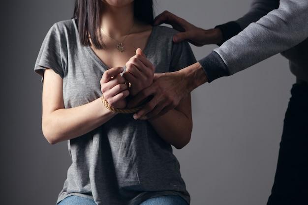 남자가 묶인 여자를 공격