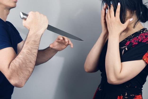 Мужчина напал на женщину с ножом на сером фоне