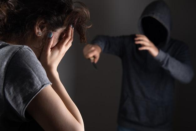 Мужчина напал на женщину с ножом на серой стене