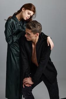 灰色の背景にイブニングドレスを着た男性と女性。高品質の写真