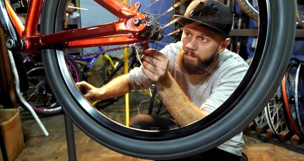 수염을 가진 남자 자전거 정비사가 그의 작업장에서 산악 자전거를 조립합니다.