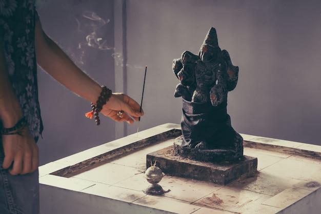 남자는 이교도 토템에 향기로운 흡연 막대기를 가져옵니다. 검은 배경에 힌두교 신 ganesh입니다. 향 연기와 함께 나무 테이블에 동상. 향기로운 지팡이