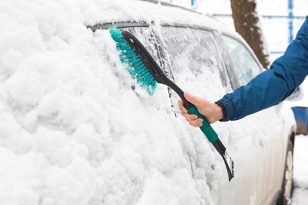 降雪後、男性が車から雪を払います。