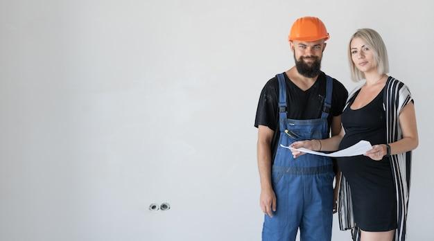 女性のクライアントを持つ男性ビルダーが修理計画を検討しています。妊娠中の女の子。子供の誕生前のアパートの改修の概念。バナー。テキストの場所