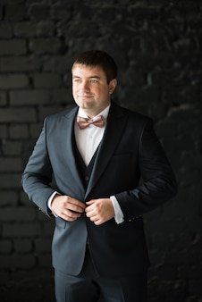 黒の背景にスーツのボタンをボタンで留める男
