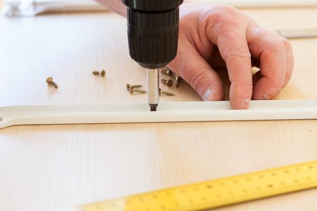 男は家具の組み立てを行い、木のシートに穴を開けます