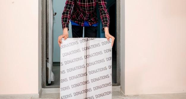 男性が募金箱を持って、チャリティー、人間の助け、援助として子供たちに寄付します