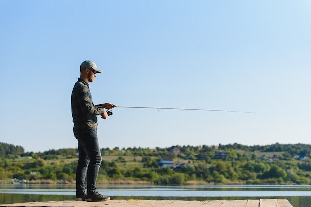 Мужчина ловит рыбу на спиннинг летом