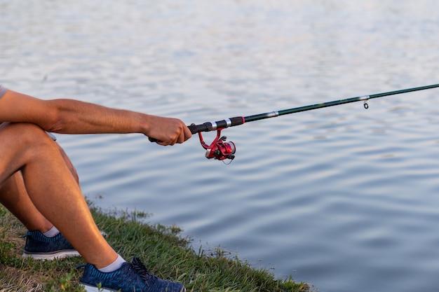 テキスト用のスペースがある湖や池から釣りをしているときに、男が魚を捕まえて釣り竿を引っ張る
