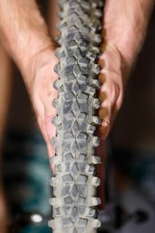 남자는 자전거 바퀴에 카메라를 변경합니다. 스파이크 자전거 챔버