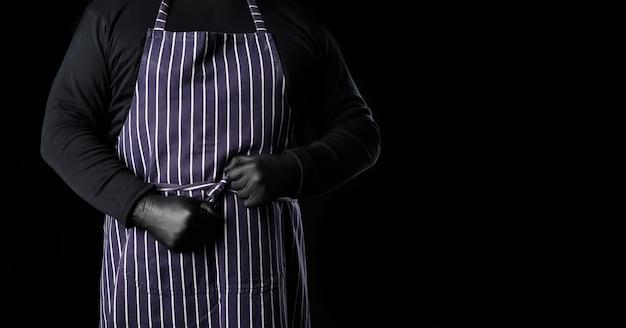 Мужчина-повар в полосатом синем фартуке и черной одежде стоит на черном фоне, место для надписи