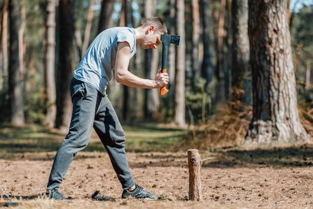 Мужчина рубит дрова в лесу