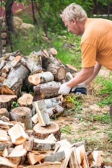 Мужчина рубит дрова большим топором во дворе своего дома, добывая горючее на зиму на