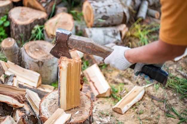 Мужчина рубит дрова большим топором заготовка топлива на зиму для отопления жилья выборочно