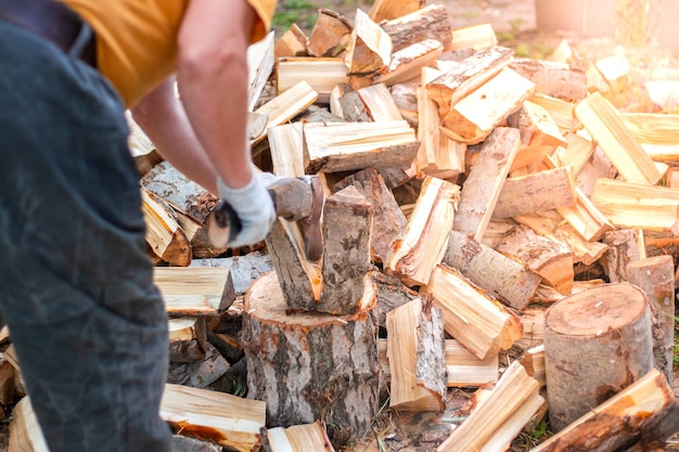 Мужчина рубит дрова топором заготовка топлива для печи и камина на зиму