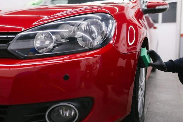 スポンジ、車の詳細(またはvaleting)の概念で車を掃除する人。セレクティブフォーカス。