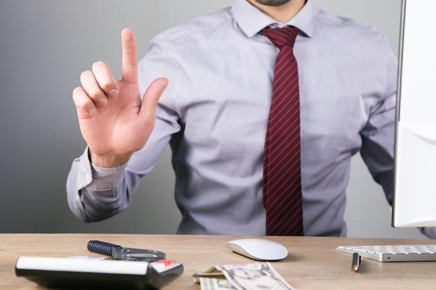Мужчина нажимает на виртуальный экран, сидя за своим столом.