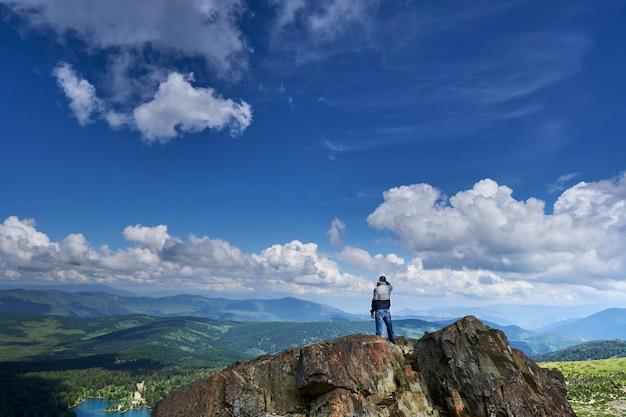 男登山家が崖の端に立ち、湖と山々を遠くから眺めます。アルタイロシア
