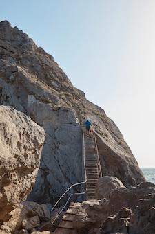 Мужчина поднимается по каменной лестнице в скале, море и горы, скалы