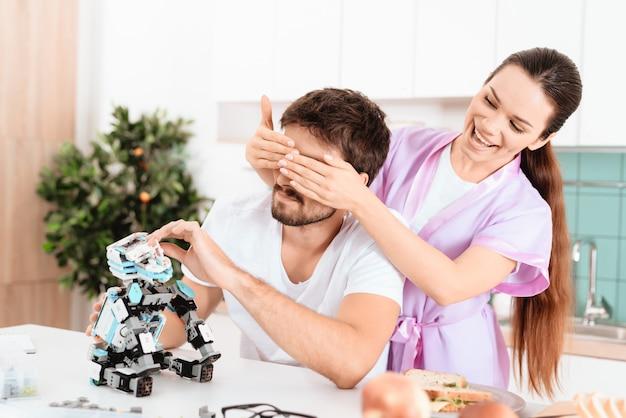 Мужчина собирает робота на кухне.
