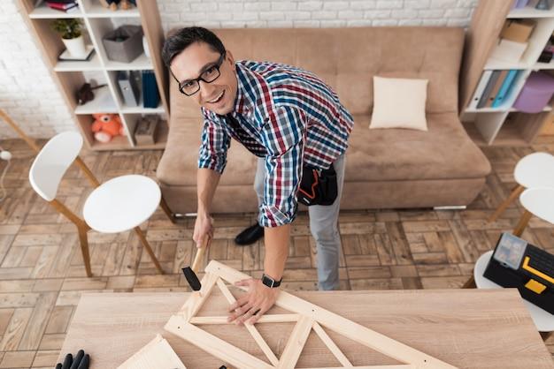 Мужчина собирает мебель дома и смотрит вверх.