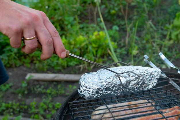 Мужчина готовит на огне мясные колбаски, грибы в беконе и рыбу в фольге.