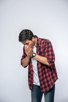 咳をして手で口を覆っている男性。